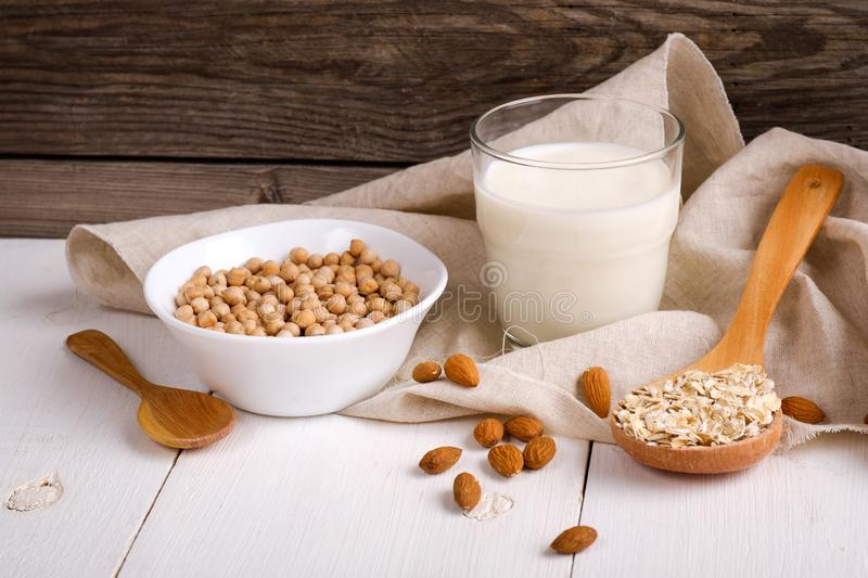 Vegan non dairy milk in glass and milk alternatives ingredients like a nut, almond, soy, oat on wooden table with kitchen towel. stock images