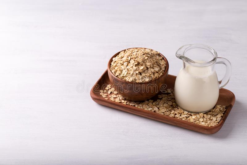Non dairy oat milk. Vegan non dairy oat milk flakes on white wooden background. Healthy eating royalty free stock photo