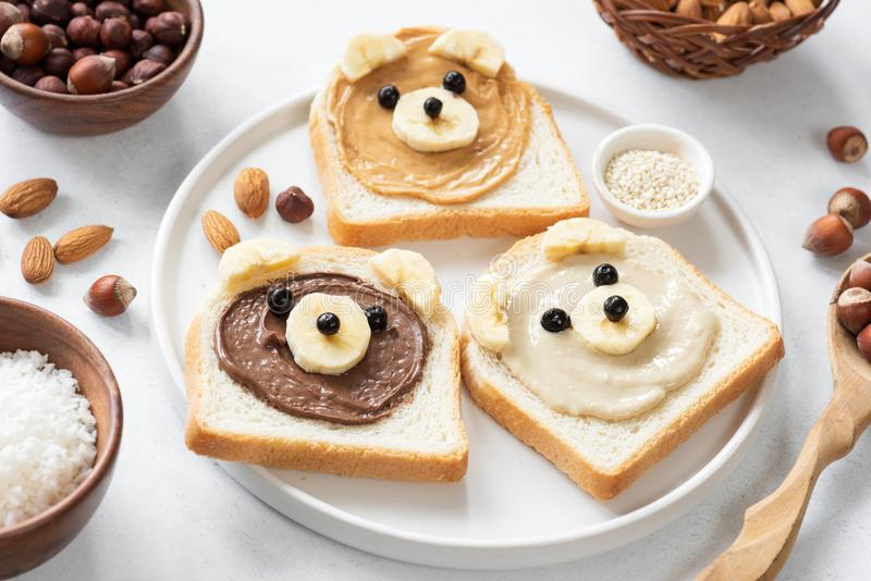 Vegan nut butter toasts with animal faces. Healthy breakfast for kids. Selective focus. Concept of vegan, healthy lifestyle, peanut butter banana, food art and stock photos