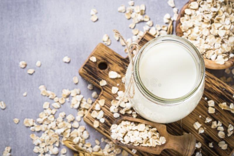 Vegan oat milk, non dairy alternative milk. Oat flakes milk in glass jar on stone table. Vegan non dairy alternative milk stock image