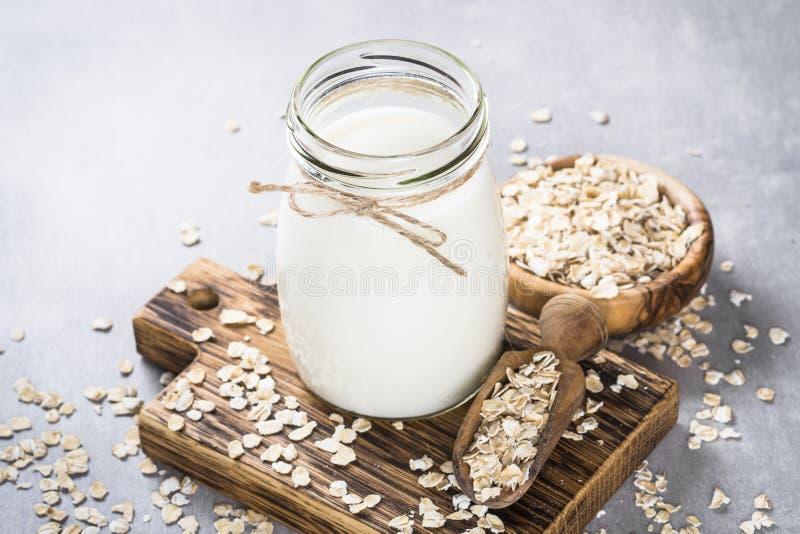 Vegan oat milk, non dairy alternative milk. Oat flakes milk in glass jar on stone table. Vegan non dairy alternative milk stock images
