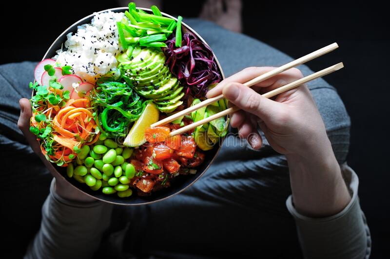 Vegan poke bowl with marinated watermelon, edamame, avocado, seaweed and carrot noodles. Man holding plate and chopstick stock photo