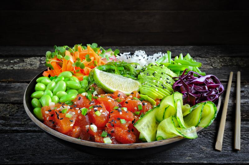 Vegan poke bowl with marinated watermelon, edamame, avocado, seaweed and carrot noodles stock photography