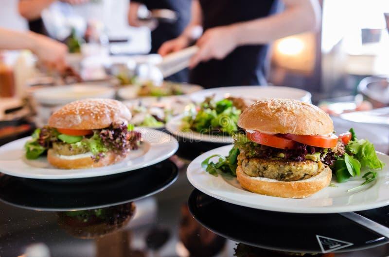 Vegan quinoa burger in a restaurant. Vegan quinoa burger at restaurant, woman on background stock photography