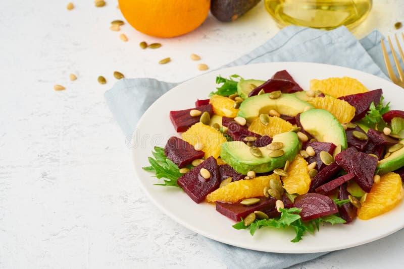 Vegan salad with beet curd avocado orange feta ricotta and pumpkin seeds, keto ketogenic dash diet, closeup copy space, pastel. Salad with beet, curd, avocado royalty free stock images