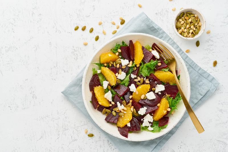 Vegan salad with beet curd avocado orange feta ricotta and pumpkin seeds, keto ketogenic dash diet, top view copy space, pastel. Salad with beet, curd, avocado royalty free stock photography