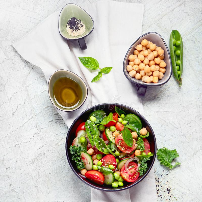 Vegan salad with cucumber, tomato, spinach, lettuce, onion, green pea and chickpea stock image