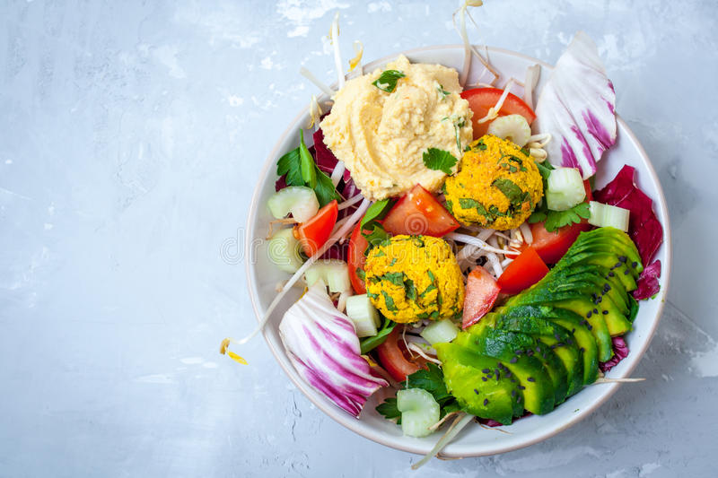 Vegan salad with falafel, hummus, vegetables. View top on gray concrete background. Vegan Food Concept royalty free stock photos