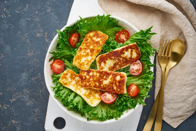 Vegan salad with fried halloumi and tomatoes, dark background, top view royalty free stock images