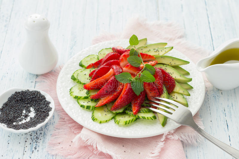 Vegan salad from strawberry, cucumber and avocado with poppy seeds royalty free stock photography