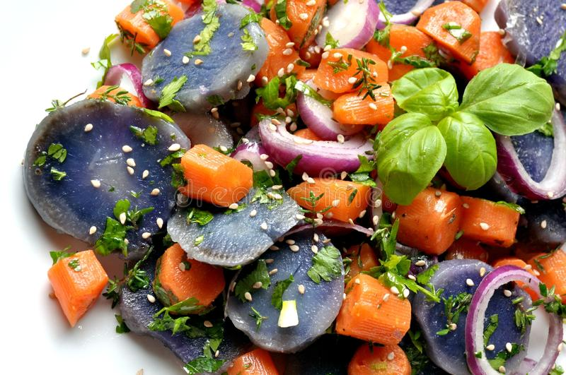 Vegan salad with violet potato, carrots and onion. Violet potato and carrot salad with onion. vegan, vegetarian dish with sesame on a white plate. copy space for royalty free stock photo
