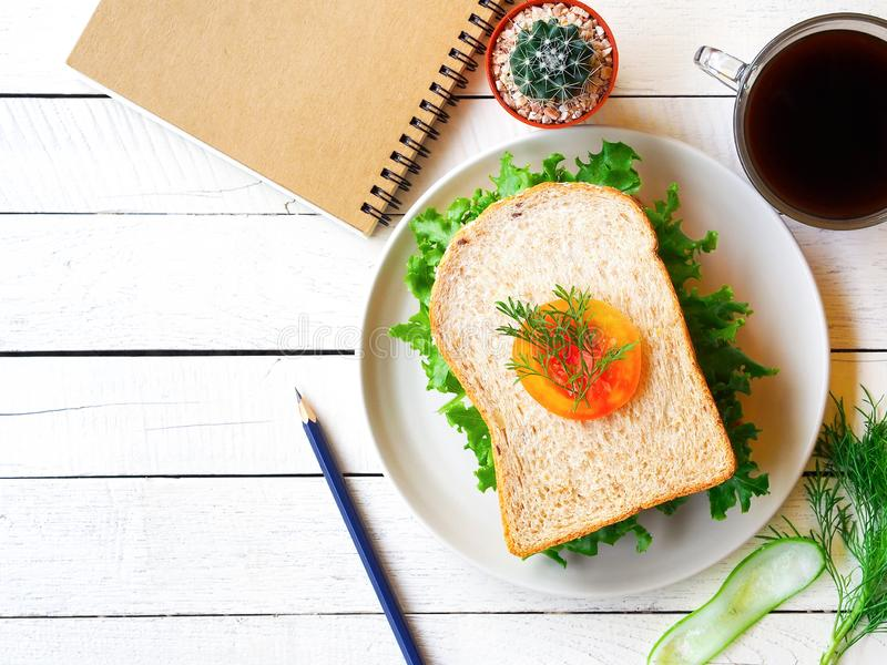 Vegan sandwich breakfast and notebook. Vegan sandwich, black coffee cup, notebook and pencil on white wooden table in top view with copy space on the left side royalty free stock photos
