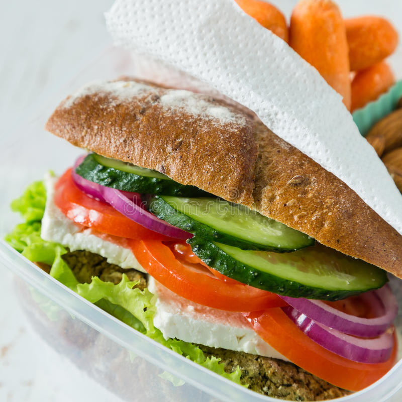 Vegan sandwich in lunch box with carrots and nuts royalty free stock photography