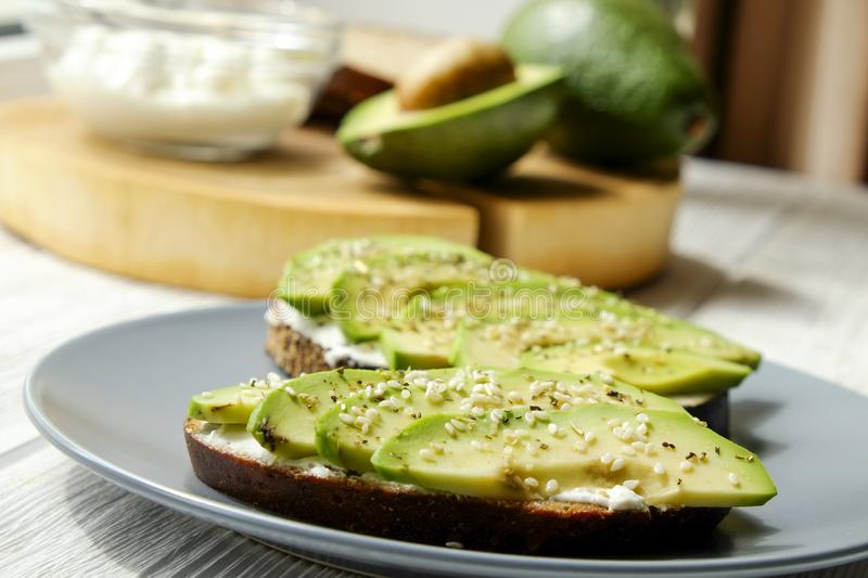 Vegan sandwich, rye bread toast, avocado slices, vegenaise sauce & raw arugula. Toasted sourdough, eggless mayonnaise, wooden tabl royalty free stock image