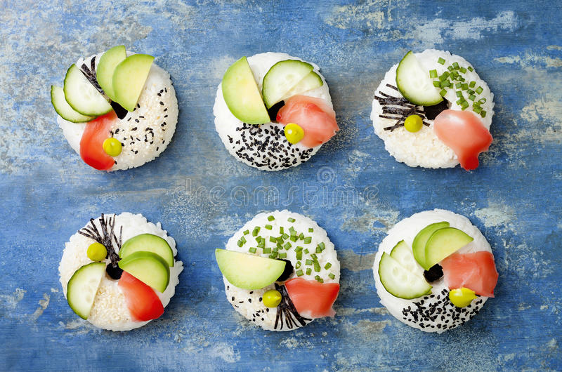 Vegan sushi donuts set with pickled ginger, avocado, cucumber, chives, nori and sesame on blue background. Sushi-food hybrid trend. Vegan sushi donuts set with stock photo
