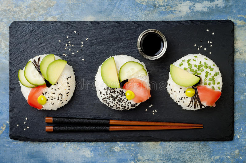 Vegan sushi donuts set with pickled ginger, avocado, cucumber, chives, nori and sesame on blue background. Sushi-food hybrid trend. Vegan sushi donuts set with royalty free stock images