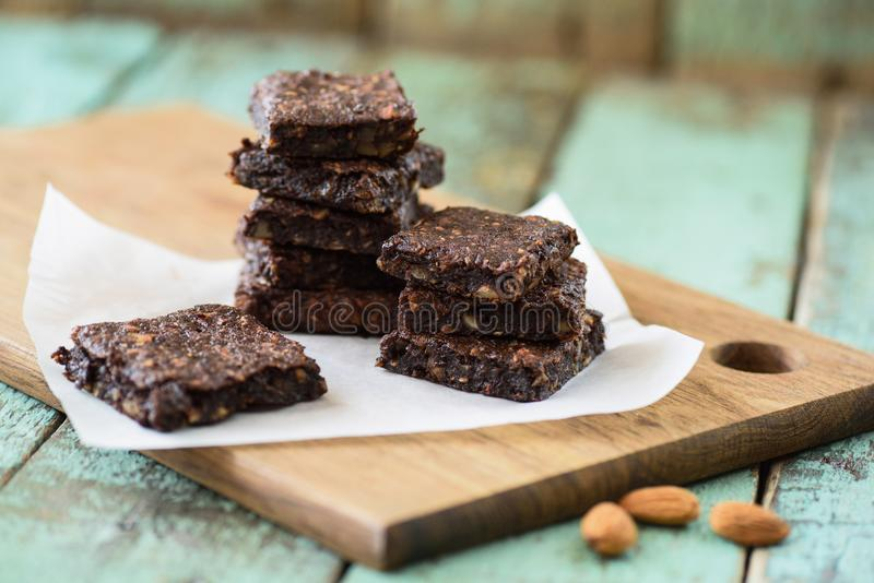 Vegan sweets. Stack of homemade low calorie no sugar brownies wi. Th almonds on wooden board selective focus royalty free stock photography