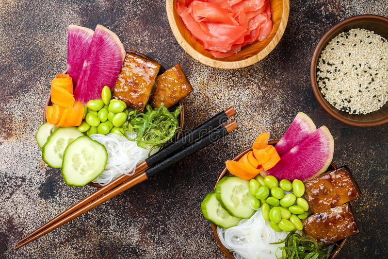 Vegan tofu poke bowls with seaweed, watermelon radish, cucumber, edamame beans and rice noodles. Copy space royalty free stock images