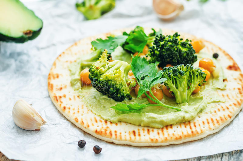 Vegan tortilla with roasted broccoli and chickpeas and avocado s stock photos