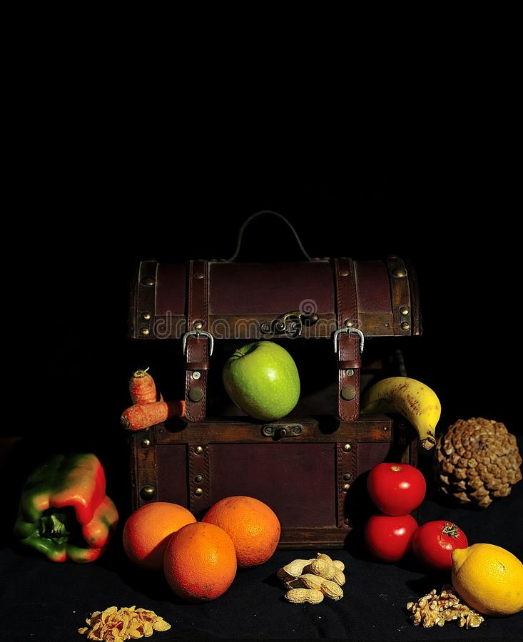 Vegan treasure, some vegetarian foods around an antique chest on black surface. stock photo