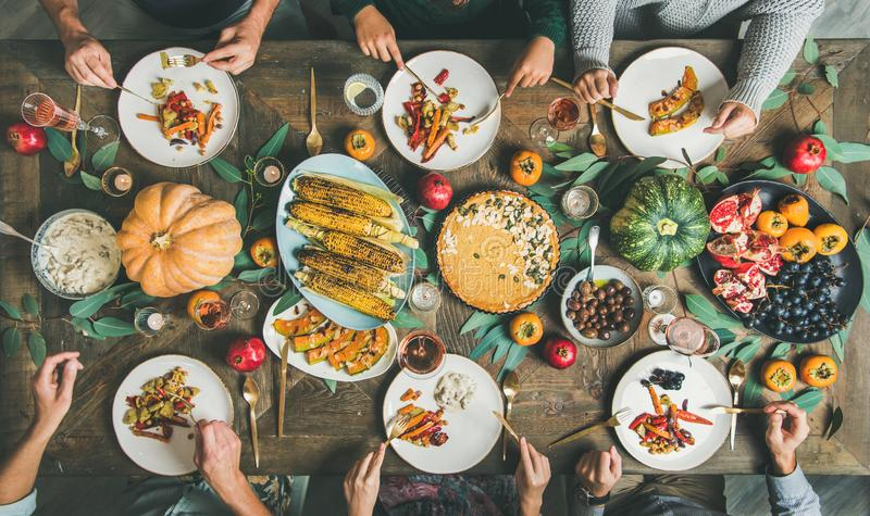 Friends eating at Thanksgiving Day table with vegetarian snacks. Vegan or vegetarian Thanksgiving, Friendsgiving holiday celebration. Flat-lay of friends eating stock image