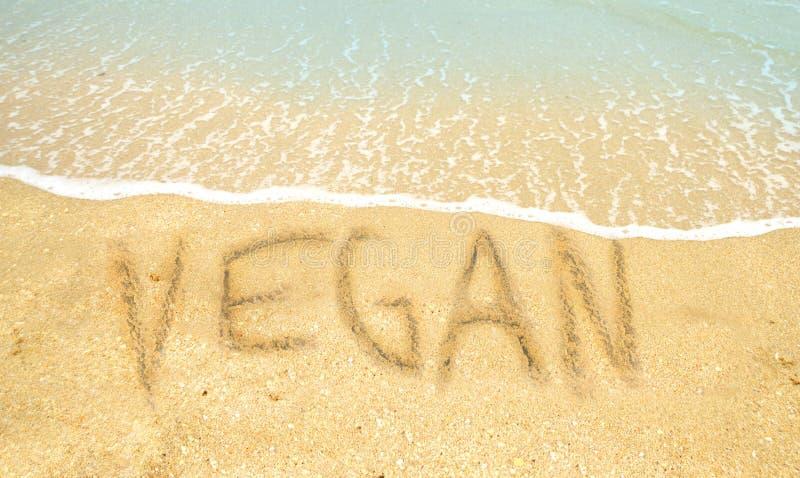Vegan word written on beach stock photo