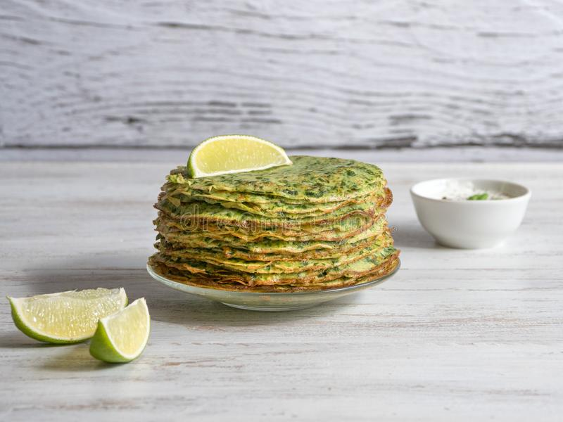 Vegan zucchini pancakes on a white wooden table stock image