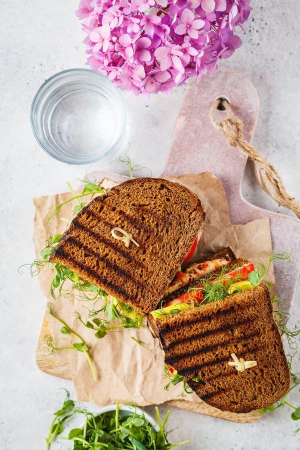 Veganisches Sandwich mit Tofu, Hummus, Avocado, Tomaten und Sprossen lizenzfreies stockbild