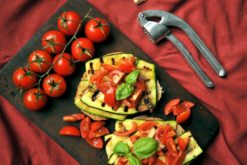 Veganist, alkalische, gezonde voedsel met geroosterde courgette en tomaat stock afbeelding
