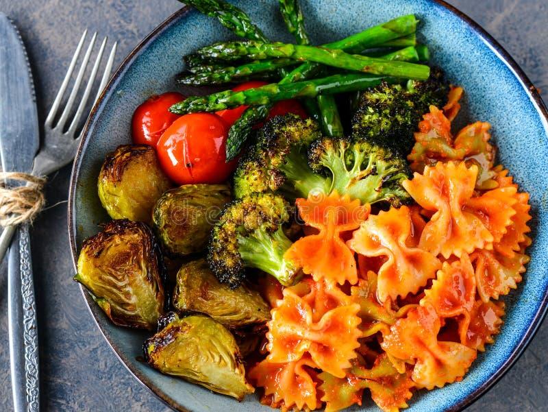 Veganist farfalle deegwaren met geroosterde groenten stock foto's