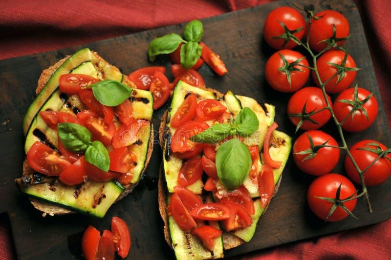 Veganist gezond voedsel met geroosterde courgette en verse tomaat stock afbeelding