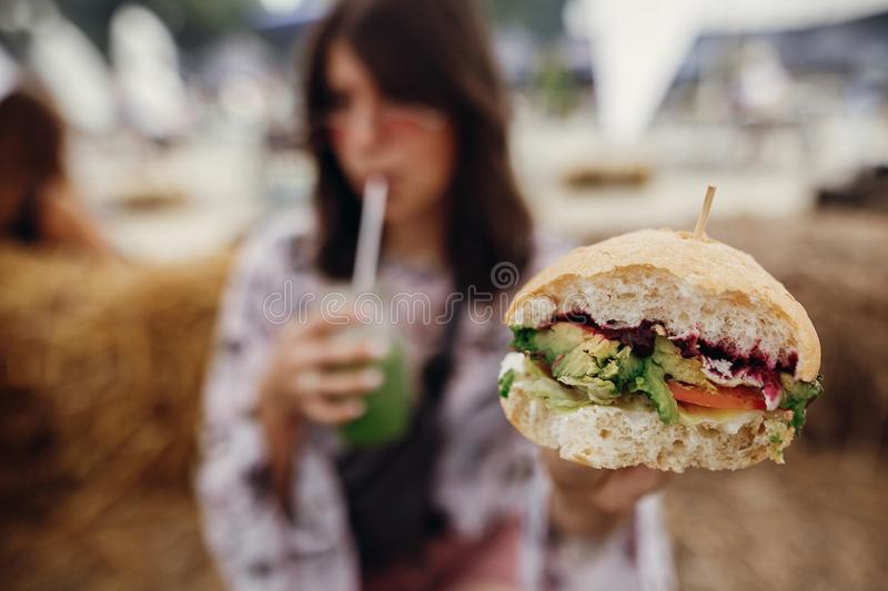 Veganisthamburger in handenclose-up Modieus hipstermeisje die heerlijke veganisthamburger en smoothie in glaskruik houden in hand stock fotografie