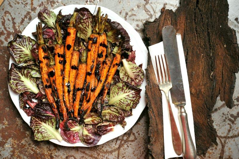 Veganistmaaltijd met geroosterde wortelen en bittere salade stock foto