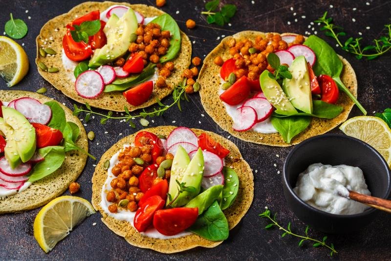 Veganisttaco's met gebakken kekers, avocado, saus en groenten op donkere achtergrond stock afbeeldingen