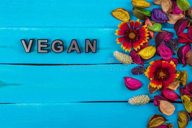 Veganistwoord op blauw hout met bloem royalty-vrije stock fotografie