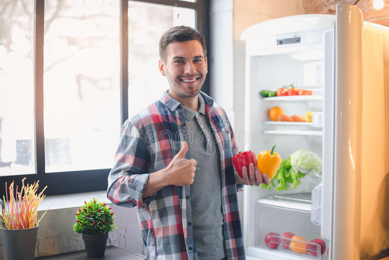 Vegano del hombre joven con los productos alimenticios de alimento biológico sanos imagen de archivo libre de regalías