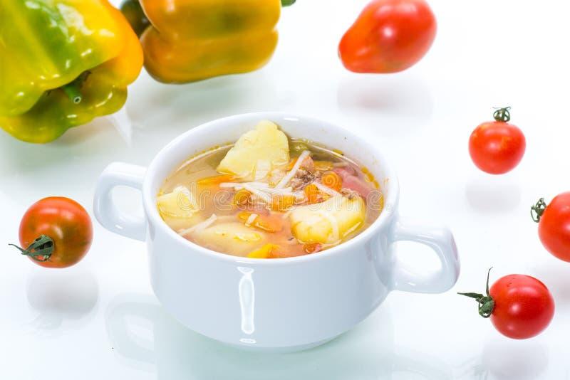 Vegetabilisk soppa med nudlar, tomater, paprika och andra grönsaker i en platta arkivfoto