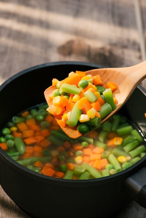 Тушеное мясо овоща в черном баке на салфетке цвета на деревянной предпосылке стоковая фотография