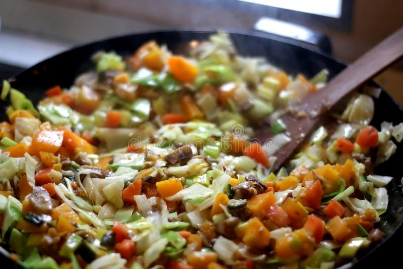 Stir Fry. Vegetable and champignon mushroom stir fry in wok. Selective focus stock photography