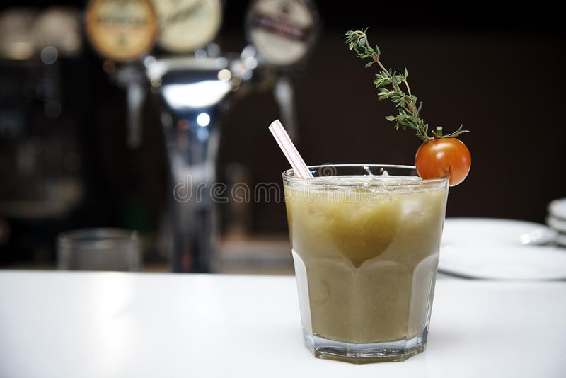 Vegetable cocktail in a glass with a tube adorned with a tomato with a branch against the background of a blurry bar stock photos
