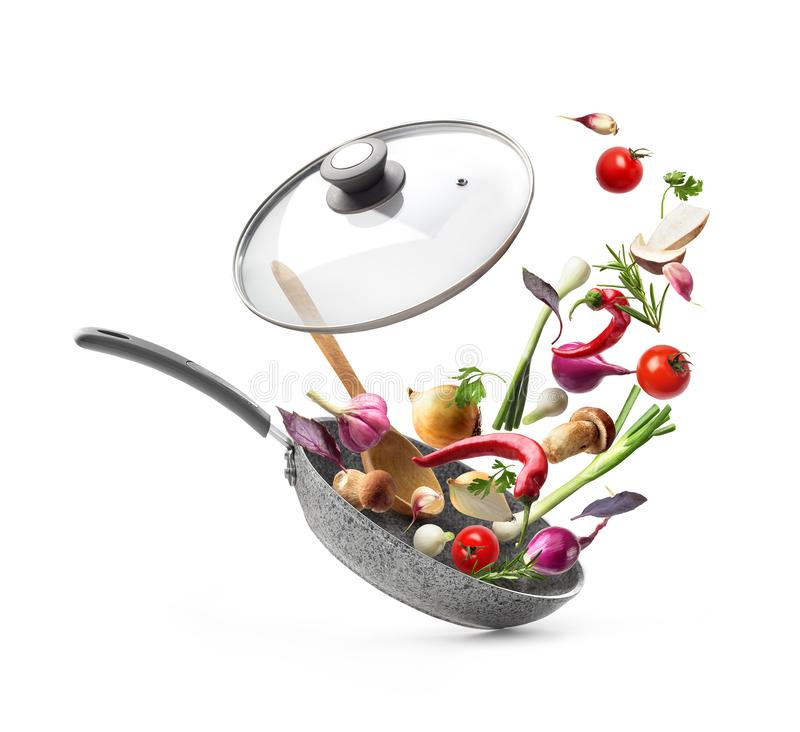 Frying pan with lid and flying vegetables, isolated on white background. Vegetable composition. Frying pan with lid and flying vegetables, isolated on white stock photo