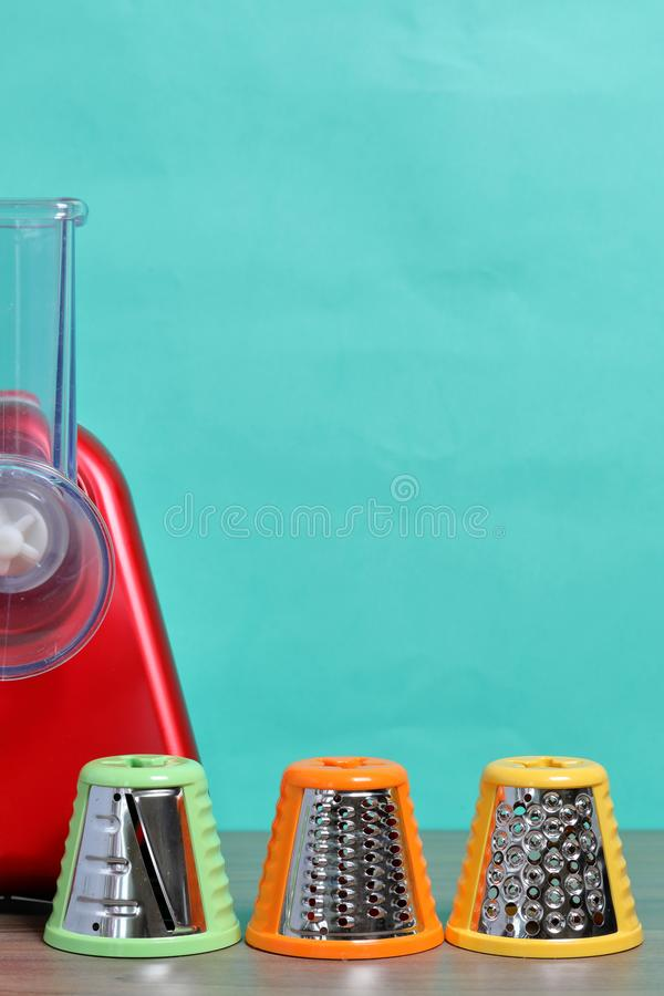 Vegetable cutter with various nozzles. Standing on the tabletop. Against the background of mint color.  stock images