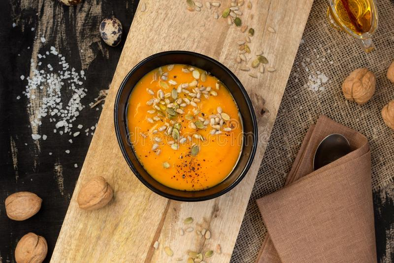 Vegetable dish pumpkin soup with seeds on a wooden cutting board. Top view stock photo