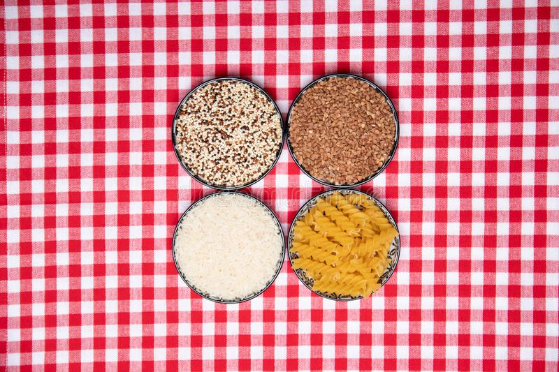 Vegetable food. A frame of four bowls with buckwheat, noodles, rice and quinoa on a red checkered tablecloth. Healthy eating. Top stock photography