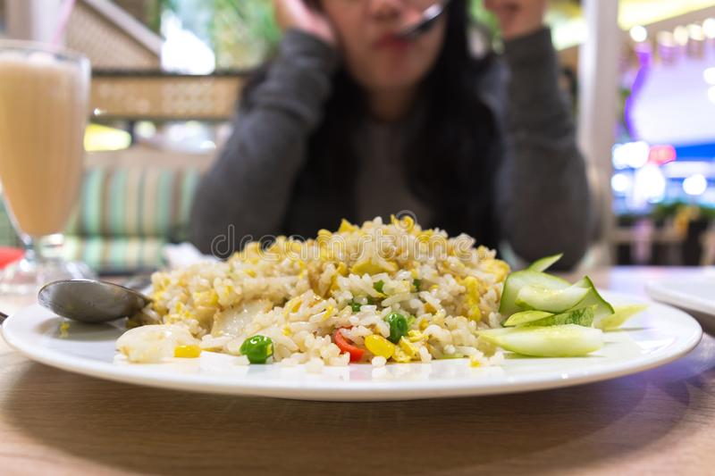 Fried rice. Vegetable fried rice on restaurant with woman on background royalty free stock image