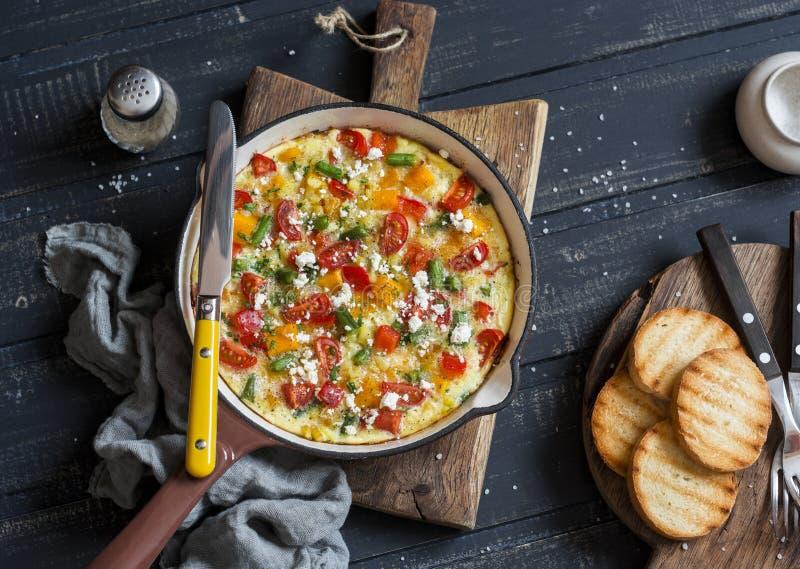 Vegetable frittata в skillet литого железа на деревянной предпосылке Очень вкусный завтрак-обед стоковые фото