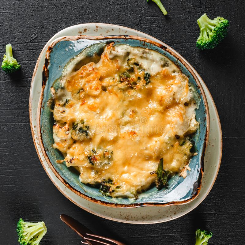 Vegetable Frittata with potato, broccoli, cheese in plate over dark background. Healthy vegan food, clean eating, dieting.  royalty free stock photo