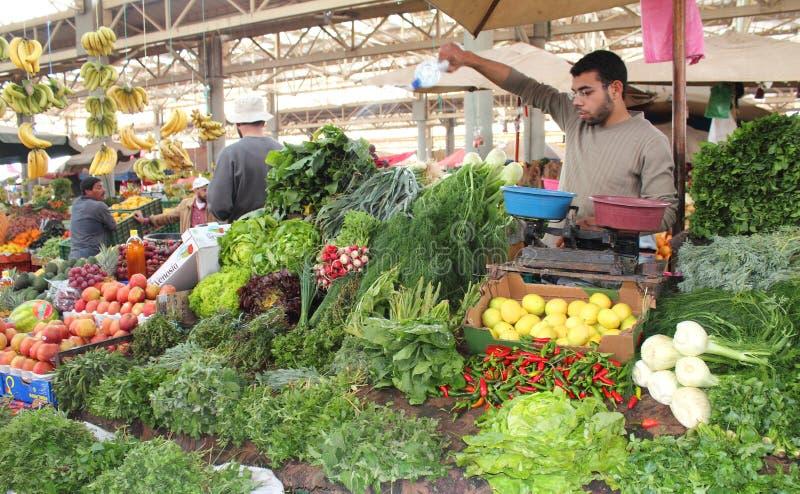 Vegetable and fruits market. Seller man watering vegetables and fruits at market in Agadir, Morocco stock image