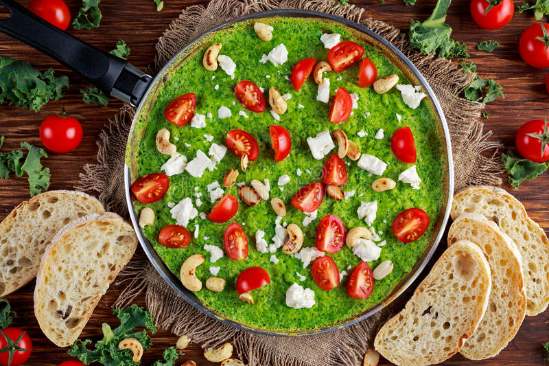 Vegetable Green Omelette with tomatoes, kale, greek cheese, olives, nuts, toast on wooden background. concept healthy food.  royalty free stock photo