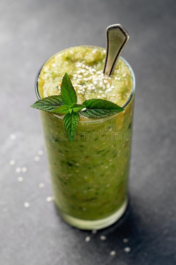 Vegetable green smoothie on a dark background. Vegetable green smoothie in a glass on a dark background stock photo